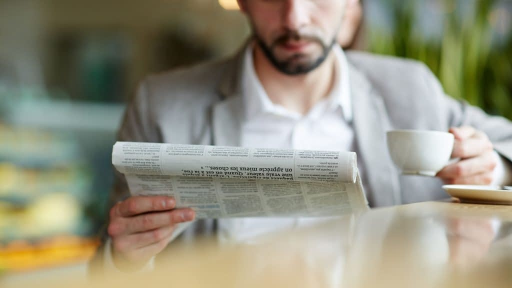 Man reading the newspaper with coffee in hand - GASB 75 makes it in the Wall Street Journal