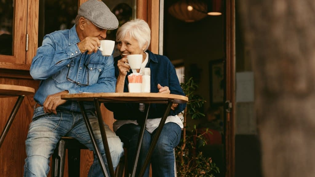 Retired couple who used to be a teacher and CPA enjoying coffee.