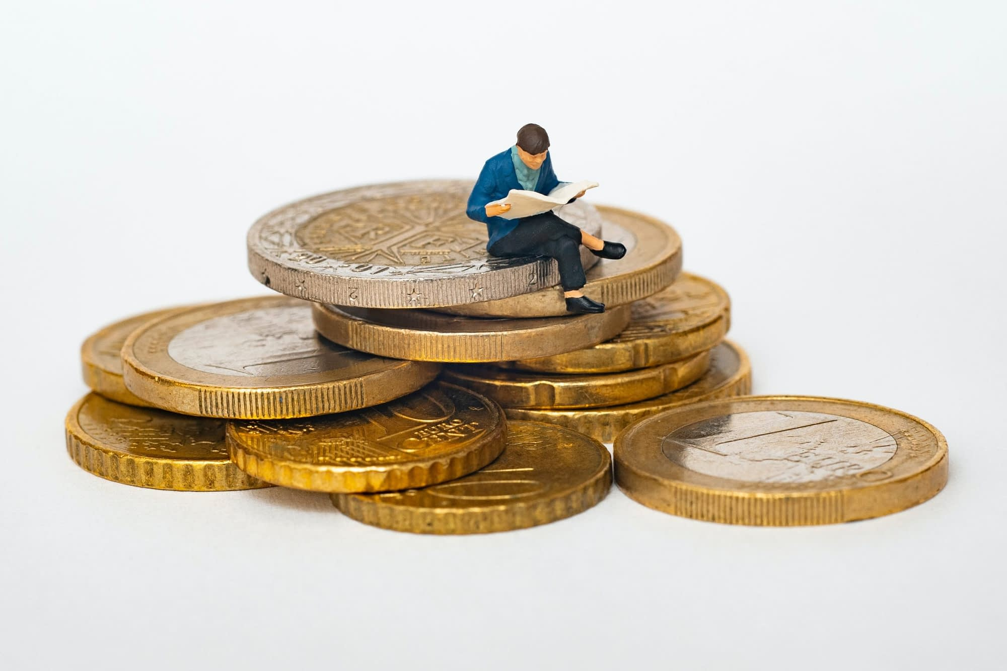 Man reading a newspaper sitting on top of very large gold coins