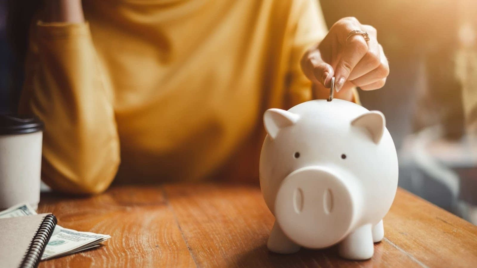 Women in a yellow top dropping a coin into a piggy bank for savings
